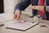 oříznutý pohled na agenta držícího ruku nad papírovým modelem domu a schránku s nápisem pojištění