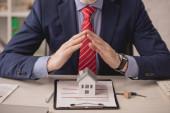 oříznutý pohled agenta držícího se za ruce nad papírovým modelem domu a schránkou s nápisem pojištění