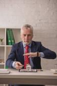 vousatý realitní makléř drží ruku nad kartonem dům model na schránce poblíž kláves na stole