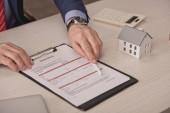 ořezaný pohled agenta držícího pero poblíž schránky s nápisem pojištění a papírovým modelem domu