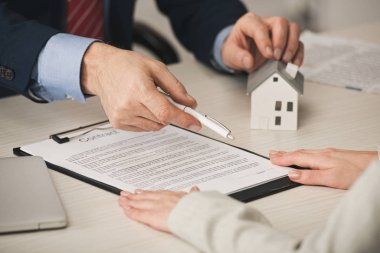 cropped view of agent giving pen to woman while touching house model