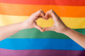 Photo cropped view of woman showing heart with hands near lgbt flag, human rights concept