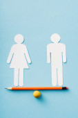 paper figures of couple as gender equality on pencil with ball isolated on blue, sexual equality concept