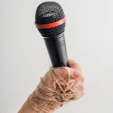 cropped view of woman with tied hand holding microphone isolated on white, freedom of speech concept