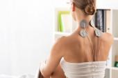 Pohled na ženu s elektrodami na krku při léčbě elektrod na klinice