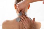 Terapeuti upevňují elektrody na krk pacienta během elektroterapie izolované na bílo