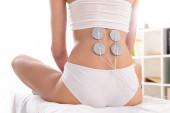 Vágott kilátás nő elektródák hátán ül a masszázs kanapén a klinikán