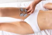 Top view az orvos beállítása elektródák beteg láb masszázs kanapén klinikán