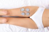 Horní pohled na mladou ženu v kalhotkách ležících na masážním gauči při elektrodové léčbě nohou