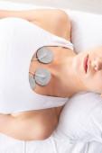 Horní pohled na ženu s elektrodami na hrudi při elektroterapii na masážním gauči na šedém pozadí