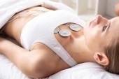 Selektivní zaměření atraktivní ženy ležící na masážní pohovce při elektrodové terapii hrudníku na klinice