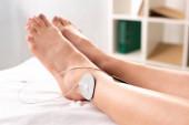 Pohled na ženu ležící na masážním gauči s elektrodami na noze na klinice