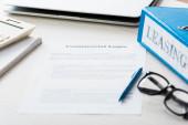 Fotografie selektive Fokussierung der Mappe in der Nähe des Dokuments mit gewerblichem Leasingaufdruck auf dem Schreibtisch