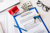 Draufsicht auf Dokument mit gewerblichem Leasingaufdruck auf Klemmbrett in der Nähe von Schlüsseln, Geld, Hausmodell, Stift und Brille