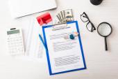 horní pohled na dokument s komerčním pronájmem nápisy na schránce v blízkosti kláves, dům model, pero, kalkulačka, lupa, peníze a brýle