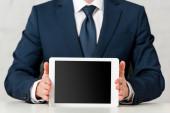 ořezaný pohled na obchodníka v obleku držícího digitální tablet s prázdnou obrazovkou na bílém