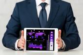 oříznutý pohled obchodníka držícího digitální tablet s mapou světa, grafy a grafy na bílém