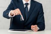 Ausgeschnittene Ansicht eines Geschäftsmannes, der Schlüssel mit Leasing-Schriftzug in der Nähe von digitalem Tablet auf weißem Hintergrund hält