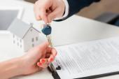 Fotografie oříznutý pohled realitního makléře dávajícího klíč ženě v blízkosti modelu kartonového domu, koncept leasingu