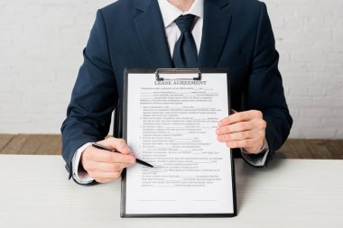 Cropped view of realtor holding clipboard with lease agreement lettering on document stock vector