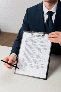 Cropped view of agent holding clipboard with lease agreement lettering and pen stock vector