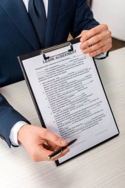 Cropped view of agent holding clipboard with lease agreement lettering near desk stock vector