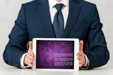 Cropped view of man in suit holding digital tablet with medical app on white stock vector
