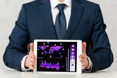 Cropped view of businessman holding digital tablet with world map, charts and graphs on screen on white stock vector
