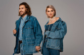 smiling man and woman in denim jackets holding hands isolated on grey