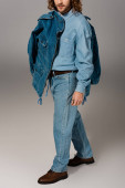 Photo cropped view of stylish man in denim shirt and jeans holding jacket on grey background