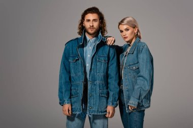 Stylish man and woman in denim jackets looking at camera isolated on grey stock vector