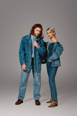 Stylish man and woman in denim jackets and jeans looking at camera on grey background stock vector