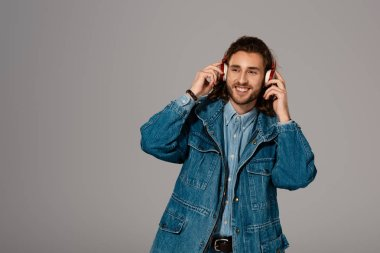 smiling man in denim jacket listening to music with headphones isolated on grey