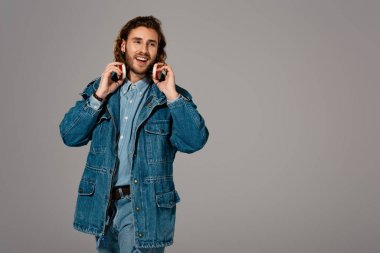 handsome and smiling man in denim jacket and jeans with headphones isolated on grey