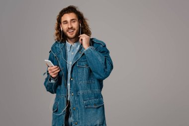 smiling man in denim jacket holding smartphone and listening to music isolated on grey