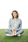 usmívající se žena s Havanem sedící na trávě štěně izolované na bílém