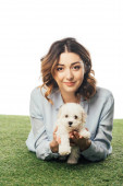 Photo smiling woman holding Havanese puppy and lying on grass isolated on white