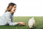 smiling woman with Havanese puppy lying on grass isolated on white