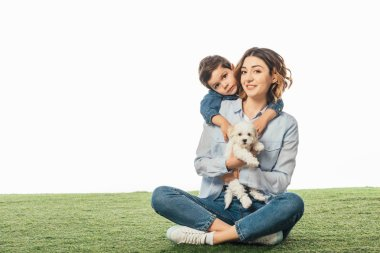 smiling mother holding Havanese puppy and son hugging her isolated on white