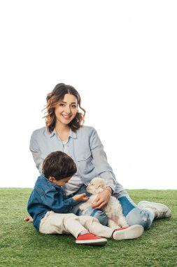 smiling mother looking at camera and son stroking Havanese puppy isolated on white