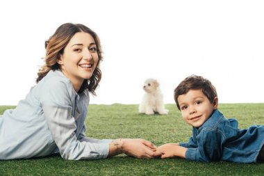 selective focus of smiling mother and son lying on grass and Havanese puppy on background isolated on white