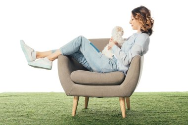 side view of woman holding Havanese puppy and sitting on armchair isolated on white