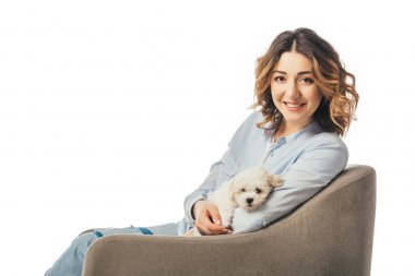 smiling woman holding Havanese puppy and sitting on armchair isolated on white