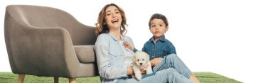 panoramic shot of smiling mother with Havanese puppy and son looking at camera isolated on white