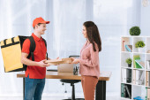 Photo Side view of delivery man giving pizza boxes to smiling businesswoman in office