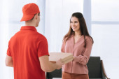 Photo Selective focus of attractive woman giving pizza boxes and smiling at courier at home