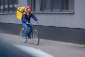 Selektivní zaměření na usměvavý doručovatel s termobatohem jízdu na kole v blízkosti budovy