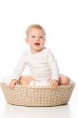 Aranyos fiú nyitott szájjal ül a takaró kosárban fehér háttér