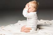 Oldalnézet aranyos gyermek borító arc és térdelés takarón elszigetelt fekete