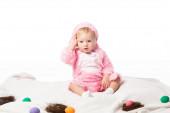 Fényképek Feldúlt gyermek nyúl jelmezt visel, megérinti a fejét a takarón színes dekorációval elszigetelt fehér